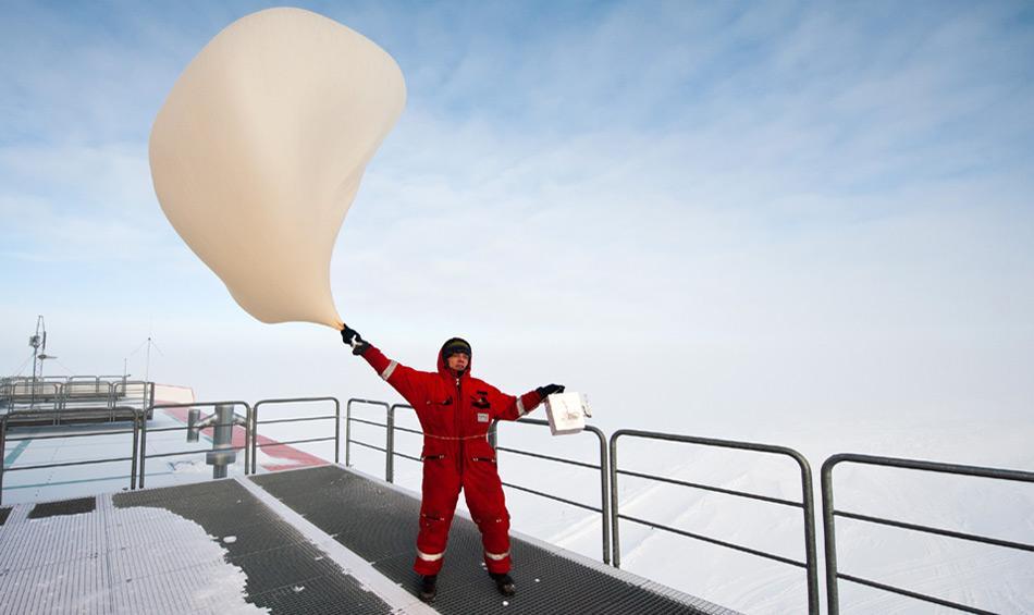 Die Ozonsondierungen werden bei jedem Wetter durchgeführt – auch wenn es an der Neumayer-Station stürmt. Auf diesem Foto lässt Thomas Schmidt, Meteorologe des Überwinterungsteams 2012 die Ozonsonde bei sehr windigen Bedingungen steigen.