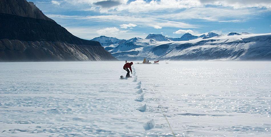 Teammitglied Daniel Baggenstoss nimmt Proben aus dem Eis. Im Hintergrund steht das Forschungscamp. © Hinrich Schaefer