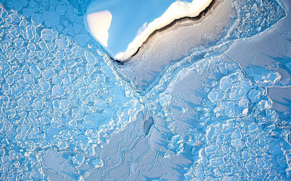 Ein Eisberg treibt im Weddellmeer durch Pfannkucheneis. So wird junges Eis genannt, das aufgrund der Wellenbewegung diese auffallend runde Form angenommen hat. Foto: IceCam / Stefan Hendricks, AWI
