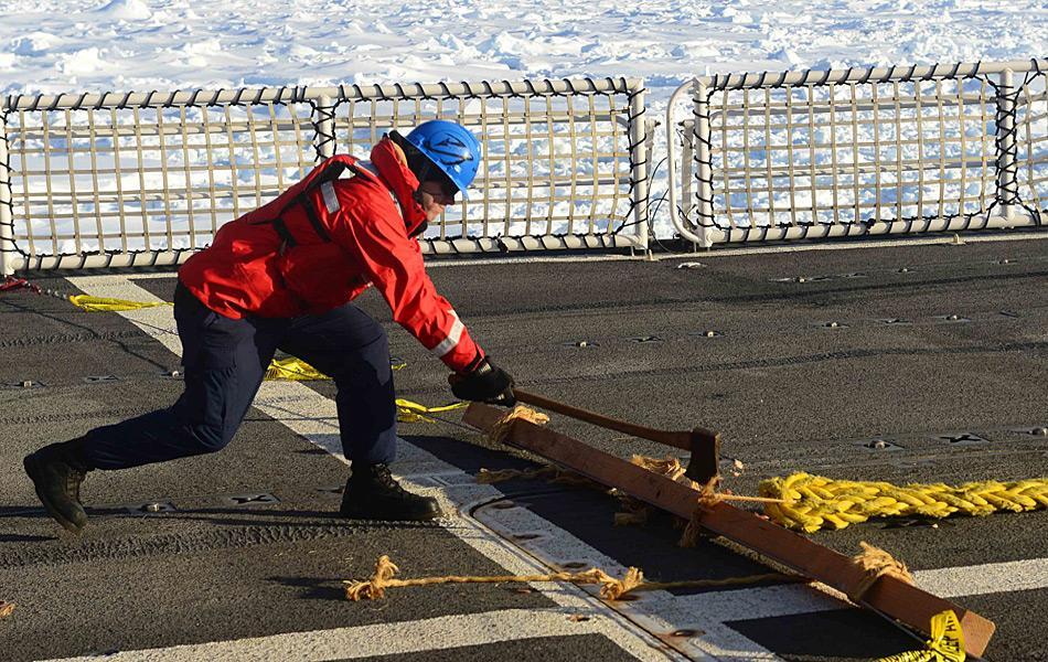 Matrose Patrick O'Grady benutzt eine Axt, um die Schleppleine, an der die «Antarctic Chieftain» hängt, zu durchtrennen. (Foto: US Coast Guard / George Degener)