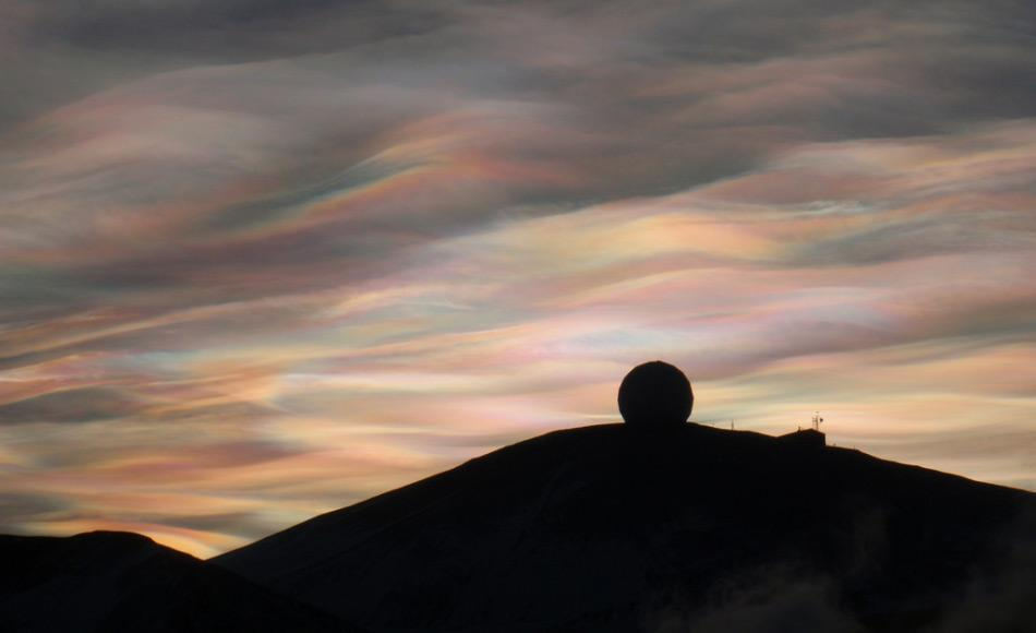 Ein herrlichen Sonnenaufgang begeisterte am 20. August Scott Base Angestellte, die zuletzt am 24. April die Sonne sahen. Polare Stratosphärenwolken (Perlmuttwolken) über der NASA Antenne bei  McMurdo Station, Antarktis (Foto: Alan Light)