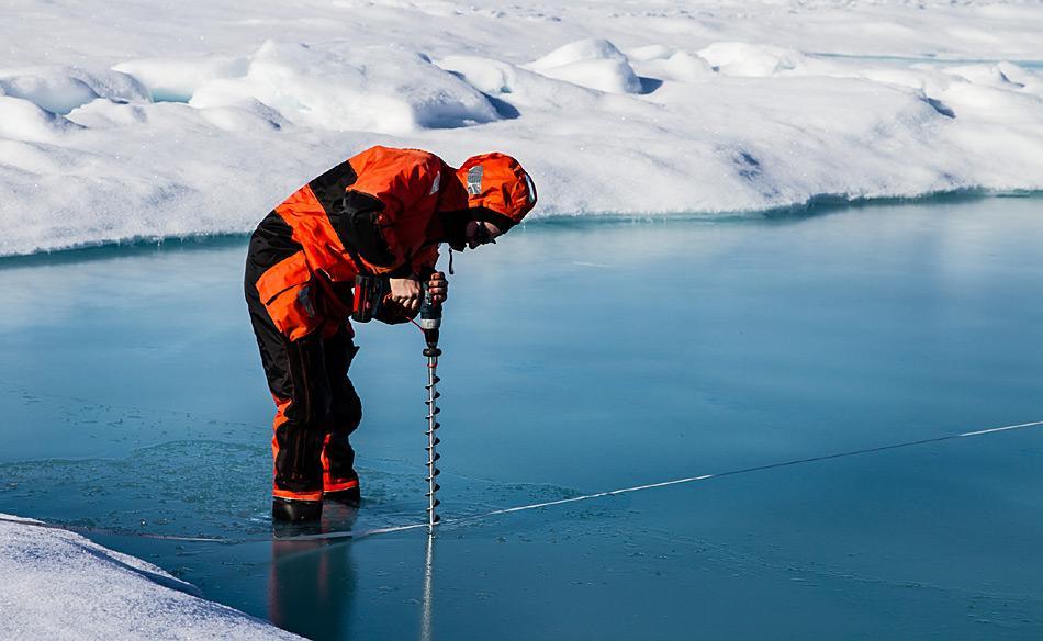AWI-Meereisphysiker Marcel Nicolaus bohrt ein Loch in den Grund eines Schmelztümpels. Die Expedition IceArc hatte zum Ziel, die Biologie. Physik und Chemie des Meereises zu untersuchen und die Auswirkungen seines Rückganges auf das gesamte Ozeansystem bis in die Tiefsee zu erforschen. Foto: AWI, Martin Schiller