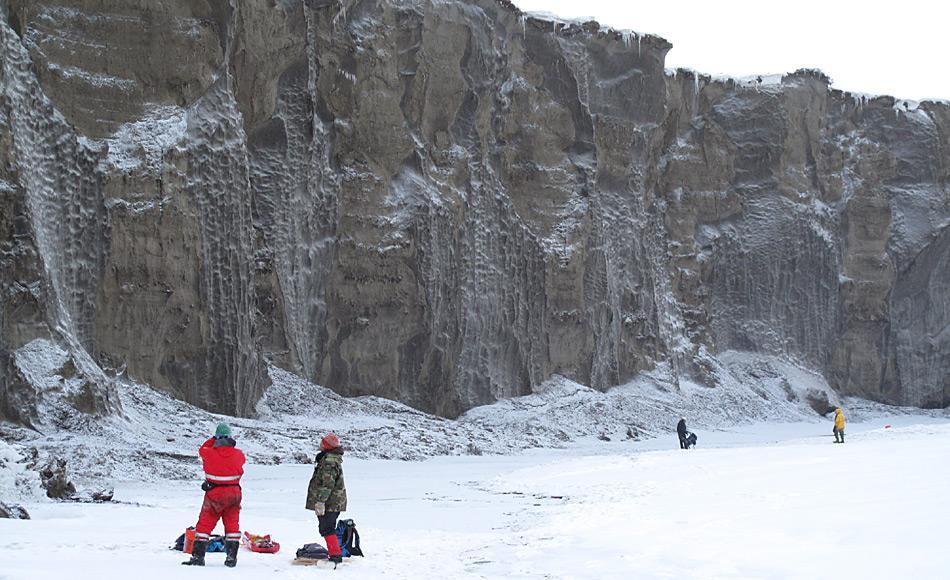 Forscher arbeiten an der 35 Meter hohen und 680 Meter langen Steilwand (Yedoma, Permafrost-Aufschluss) am Itkillit River im Norden Alaskas. Zu erkennen ist das Nebeneinander von bis zu 40 Meter langen Eiskeilen (grau) und Sedimentsäulen (bräunlich). Das Eis der Eiskeile ist bis zu 50.000 Jahre und älter. Foto: AWI, Mikhail Kanevskiy