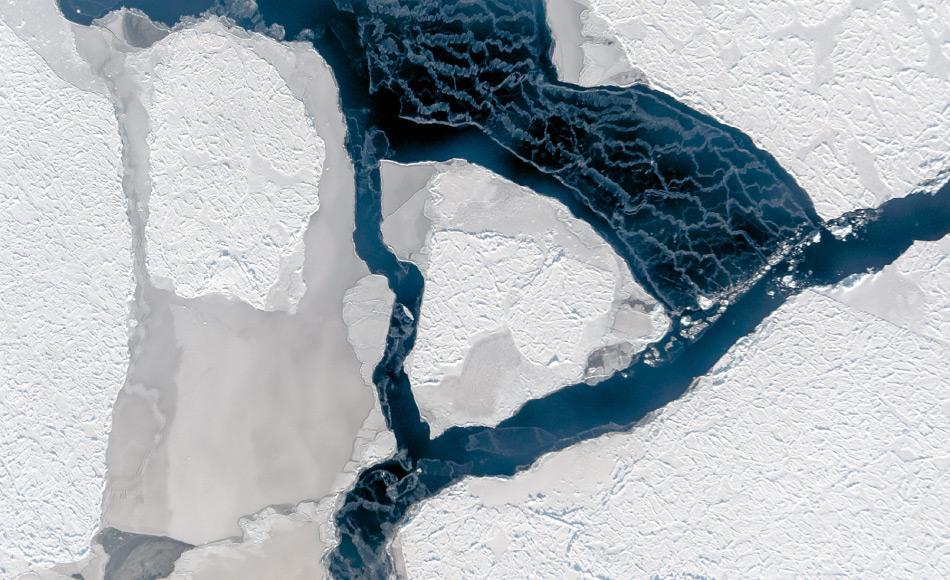 Der Wind hat ein Eisfeld auseinander getrieben und eine Fläche offenen Wassers geschaffen. Dessen Oberfläche gefriert sofort wieder, wie die weißen Schlieren verraten. Sie entstehen, wenn der Wind lose Eiskristalle verweht. Foto: IceCam/Stefan Hendricks